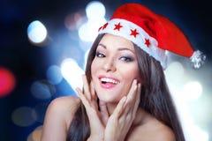 Ευτυχής γυναίκα στο καπέλο Santa στο σκοτεινό υπόβαθρο με φωτεινό ζωηρόχρωμο στοκ εικόνες