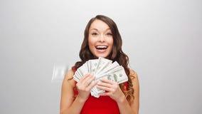 Ευτυχής γυναίκα στο κόκκινο φόρεμα με τα χρήματα αμερικανικών δολαρίων απόθεμα βίντεο