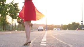 Ευτυχής γυναίκα στο κόκκινο φόρεμα που χορεύει και που γυρίζει γύρω στο δρόμο απόθεμα βίντεο