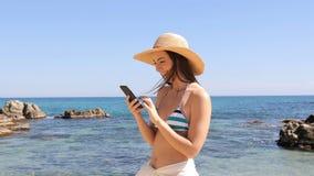 Ευτυχής γυναίκα στο μπικίνι που χρησιμοποιεί το τηλέφωνο στην παραλία φιλμ μικρού μήκους