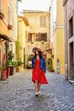 Ευτυχής γυναίκα στο φόρεμα που περπατά στην παλαιά οδό της Ρώμης στοκ εικόνες