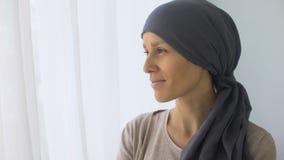Ευτυχής γυναίκα στο headscarf που κοιτάζει στο παράθυρο, αποκατάσταση μετά από τη θεραπεία του καρκίνου φιλμ μικρού μήκους