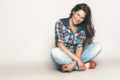 Ευτυχής γυναίκα συνεδρίασης στο πουκάμισο ελέγχου Στοκ Εικόνες