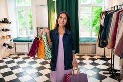 Ευτυχής γυναίκα της στάσης με τις συσκευασίες στην αίθουσα εκθέσεως στοκ εικόνες