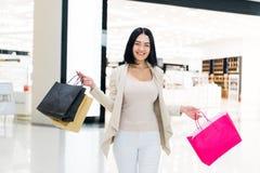 Ευτυχής γυναίκα brunette με τις ζωηρόχρωμες τσάντες αγορών στη λεωφόρο στοκ φωτογραφίες