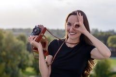 Ευτυχής γυναίκα brunette που κάνει τη φωτογραφία με την αναδρομική κάμερα στην οδό πόλεων Στοκ Φωτογραφία