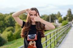 Ευτυχής γυναίκα brunette που κάνει τη φωτογραφία με την αναδρομική κάμερα στην οδό πόλεων Στοκ Εικόνα