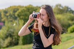 Ευτυχής γυναίκα brunette που κάνει τη φωτογραφία με την αναδρομική κάμερα στην οδό πόλεων Στοκ φωτογραφία με δικαίωμα ελεύθερης χρήσης