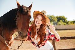 Ευτυχής γυναίκα cowgirl που στέκεται με το άλογο και που παρουσιάζει σημάδι ειρήνης Στοκ φωτογραφία με δικαίωμα ελεύθερης χρήσης