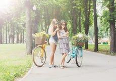 Ευτυχής γύρος κοριτσιών boho κομψός μαζί στα ποδήλατα στο πάρκο Στοκ φωτογραφία με δικαίωμα ελεύθερης χρήσης