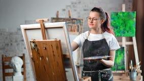 Ευτυχής δημιουργική γυναίκα ζωγράφος hipster που απολαμβάνει την εικόνα σχεδίων στον καμβά στο μέσο πυροβολισμό στούντιο τέχνης απόθεμα βίντεο
