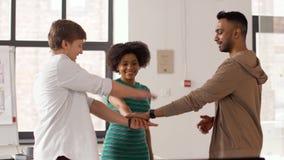 Ευτυχής δημιουργική ομάδα που συσσωρεύει τα χέρια στο γραφείο απόθεμα βίντεο