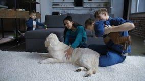 Ευτυχής διαφορετική οικογένεια που στηρίζεται με τα παιδιά και το σκυλί απόθεμα βίντεο