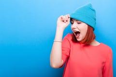 Ευτυχής δροσερή hipster γυναίκα με το στόμα της ανοικτό φορώντας ένα μπλε καπέλο Στοκ Εικόνα