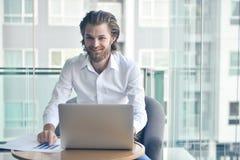 Ευτυχής δυτικός επιχειρηματίας που χρησιμοποιεί ένα lap-top στο καθιστικό Στοκ Εικόνα