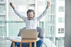 Ευτυχής δυτικός επιχειρηματίας που χρησιμοποιεί ένα lap-top στο καθιστικό Στοκ Φωτογραφία