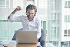 Ευτυχής δυτικός επιχειρηματίας που χρησιμοποιεί ένα lap-top στο καθιστικό Στοκ Εικόνες