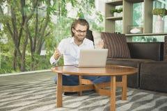 Ευτυχής δυτικός επιχειρηματίας που χρησιμοποιεί ένα lap-top στο καθιστικό Στοκ φωτογραφία με δικαίωμα ελεύθερης χρήσης