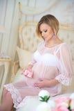 Ευτυχής εγκυμοσύνη, που περιμένει το μωρό Έγκυος συνεδρίαση κοριτσιών σε ένα κρεβάτι με τις λείες μωρών Στοκ Εικόνες