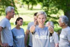 Ευτυχής εθελοντικός ξανθός με τους αντίχειρες επάνω στοκ εικόνα