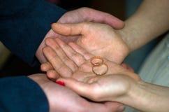 ευτυχής εκλεκτής ποιότητας γάμος ημέρας ζευγών ιματισμού Γαμήλια χρυσά δαχτυλίδια στους φοίνικες γυναικών και ανδρών Στοκ φωτογραφία με δικαίωμα ελεύθερης χρήσης