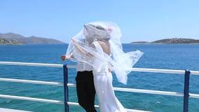 ευτυχής εκλεκτής ποιότητας γάμος ημέρας ζευγών ιματισμού Ευτυχή newlyweds στο υπόβαθρο της θάλασσας φιλμ μικρού μήκους