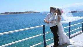 ευτυχής εκλεκτής ποιότητας γάμος ημέρας ζευγών ιματισμού Ευτυχή newlyweds κάτω από ένα πέπλο της νύφης στην παραλία φιλμ μικρού μήκους