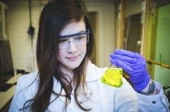 Ευτυχής εκμετάλλευση επιστημόνων γυναικών και πληρωμή στην προσοχή της επιδέξιας κίτρινης χημικής αντίδρασης στο εργαστήριο χημεί στοκ φωτογραφίες με δικαίωμα ελεύθερης χρήσης
