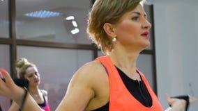 Ευτυχής εκπαιδευτικός ικανότητας γυναικών Μεσαίωνα ώριμος που κάνει τις ασκήσεις απώλειας βάρους απόθεμα βίντεο