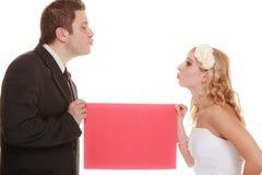 ευτυχής εκλεκτής ποιότητας γάμος ημέρας ζευγών ιματισμού κόκκινο κενό σημαδιών εκμετάλλευσης νυφών και νεόνυμφων Στοκ φωτογραφία με δικαίωμα ελεύθερης χρήσης