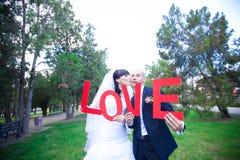 ευτυχής εκλεκτής ποιότητας γάμος ημέρας ζευγών ιματισμού στοκ φωτογραφίες