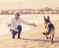 Ευτυχής ελκυστική ανώτερη γυναίκα με το γερμανικό παιχνίδι σκυλιών shepard της στην παραλία στο ηλιοβασίλεμα φθινοπώρου στοκ εικόνες