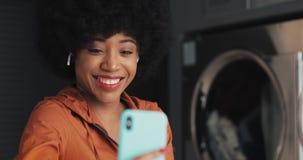 Ευτυχής ελκυστική νέα γυναίκα αφροαμερικάνων που έχει μια τηλεοπτική συνομιλία laundromat Δημόσιο πλυντήριο αυτοεξυπηρετήσεων απόθεμα βίντεο