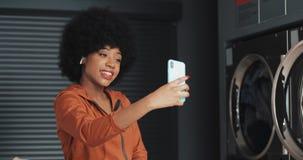 Ευτυχής ελκυστική νέα γυναίκα αφροαμερικάνων που έχει μια τηλεοπτική συνομιλία laundromat Δημόσιο πλυντήριο αυτοεξυπηρετήσεων φιλμ μικρού μήκους