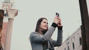 Ευτυχής ελκυστικός καυκάσιος θηλυκός τουρίστας που παίρνει τις φωτογραφίες smartphone των αρχαίων κτηρίων στην παλαιά πόλη της Βε απόθεμα βίντεο