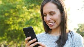 Ευτυχής ενήλικη γυναίκα που ελέγχει το έξυπνο τηλέφωνο απόθεμα βίντεο