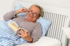 Ευτυχής ενήλικη γυναίκα με το βιβλίο που βρίσκεται στο κρεβάτι Στοκ Εικόνες