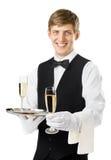 Ευτυχής εξυπηρετώντας σαμπάνια σερβιτόρων χαμόγελου σε έναν δίσκο στοκ φωτογραφία