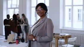 Ευτυχής επαγγελματική νέα μαύρη επιχειρησιακή γυναίκα CEO στο επίσημο κοστούμι, eyeglasses τοποθέτηση, που χαμογελά στο σύγχρονο  απόθεμα βίντεο