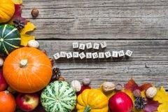 Ευτυχής επιγραφή ημέρας των ευχαριστιών με τα φρούτα και λαχανικά πτώσης με τα φύλλα σφενδάμου Στοκ Φωτογραφίες