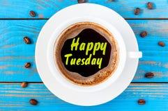 Ευτυχής επιθυμία έμπνευσης Τρίτης στο τοπ φλιτζάνι του καφέ άποψης στο μπλε ξύλινο υπόβαθρο στοκ εικόνες με δικαίωμα ελεύθερης χρήσης
