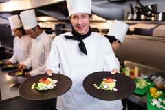 Ευτυχής επικεφαλής αρχιμάγειρας που παρουσιάζει τα πιάτα τροφίμων του Στοκ φωτογραφία με δικαίωμα ελεύθερης χρήσης