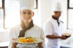 Ευτυχής επικεφαλής αρχιμάγειρας που παρουσιάζει τα τρόφιμά της Στοκ φωτογραφία με δικαίωμα ελεύθερης χρήσης