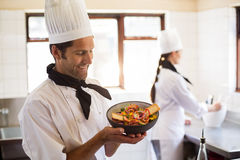 Ευτυχής επικεφαλής αρχιμάγειρας που παρουσιάζει τα τρόφιμά του Στοκ φωτογραφία με δικαίωμα ελεύθερης χρήσης