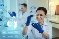 Ευτυχής επιστήμονας που χαμογελά εξετάζοντας το μπλε υγρό Στοκ φωτογραφίες με δικαίωμα ελεύθερης χρήσης