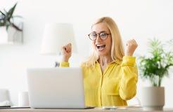 Ευτυχής επιτυχής επιχειρηματίας που θριαμβεύει με το lap-top στην αρχή στοκ φωτογραφία
