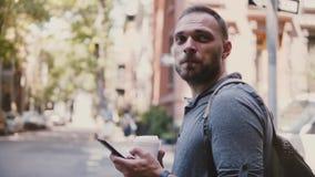 Ευτυχής επιτυχής ευρωπαϊκός ανεξάρτητος εργαζόμενος με τον καφέ χρησιμοποιώντας τον αγγελιοφόρο app smartphone, κοιτάζοντας γύρω  φιλμ μικρού μήκους