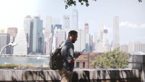 Ευτυχής επιτυχής ευρωπαϊκός ανεξάρτητος εργαζόμενος που περπατά κατά μήκος του επικού ορίζοντα του Μανχάταν στη Νέα Υόρκη με τον  φιλμ μικρού μήκους