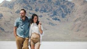 Ευτυχής επιτυχής καυκάσιος ρομαντικός περίπατος ζευγών που αγκαλιάζει και που μιλά χαρωπά στην αλατισμένη λίμνη ερήμων σε Bonnevi απόθεμα βίντεο