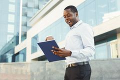 Ευτυχής επιτυχής μαύρος επιχειρηματίας που βλέπει το μεγάλο εισόδημα στην έκθεση Στοκ Εικόνες